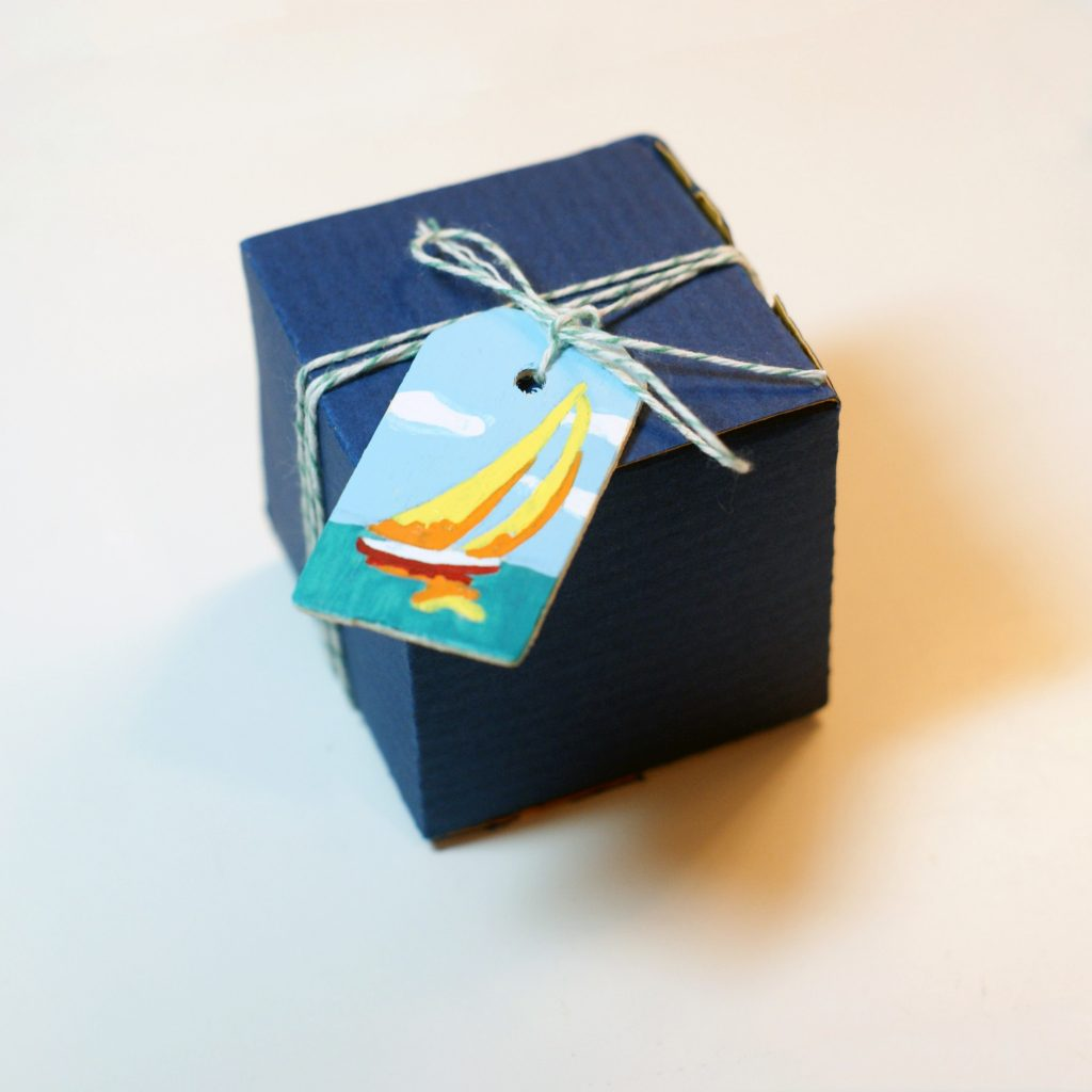 bright sailboat painted on wood tag and hung on a square package