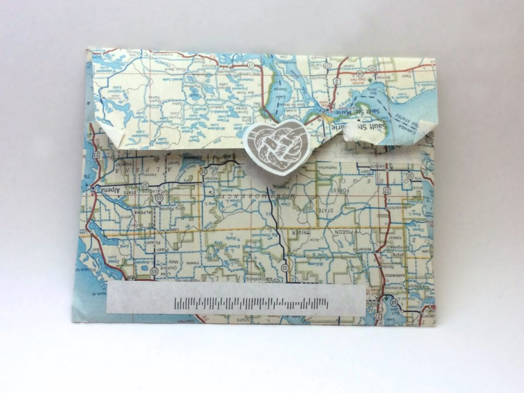 map envelope with sticker in shape of a heart with a rope heart-shaped knot illustration