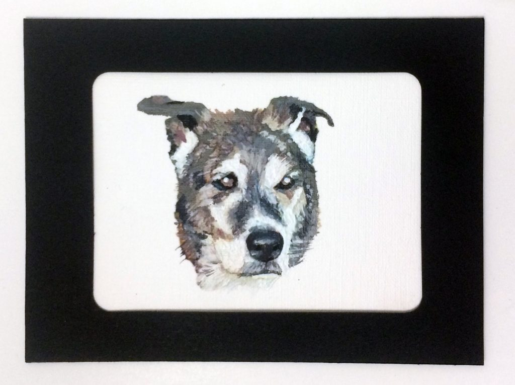 a brown and black dog face painted on paper canvas in a black frame